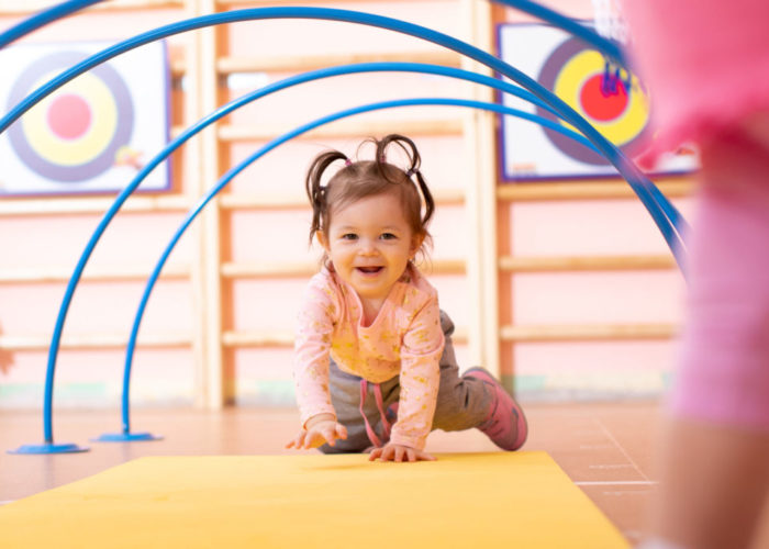 Baby crawling on floor in gym class. Lifestyle concept of children activity.