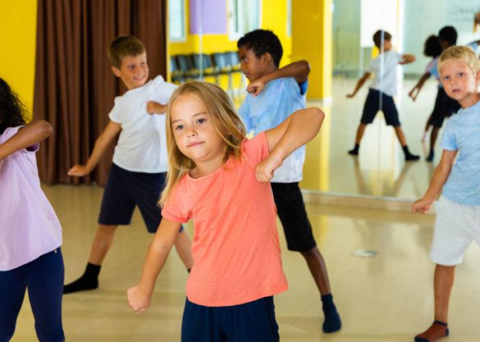 Portrait of smiling children practicing sport dance in modern da